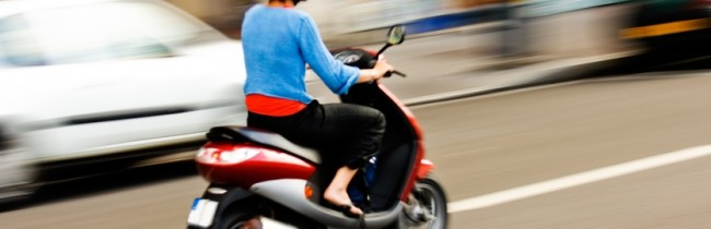 Panning shot of a young girl riding a scooter in a European city